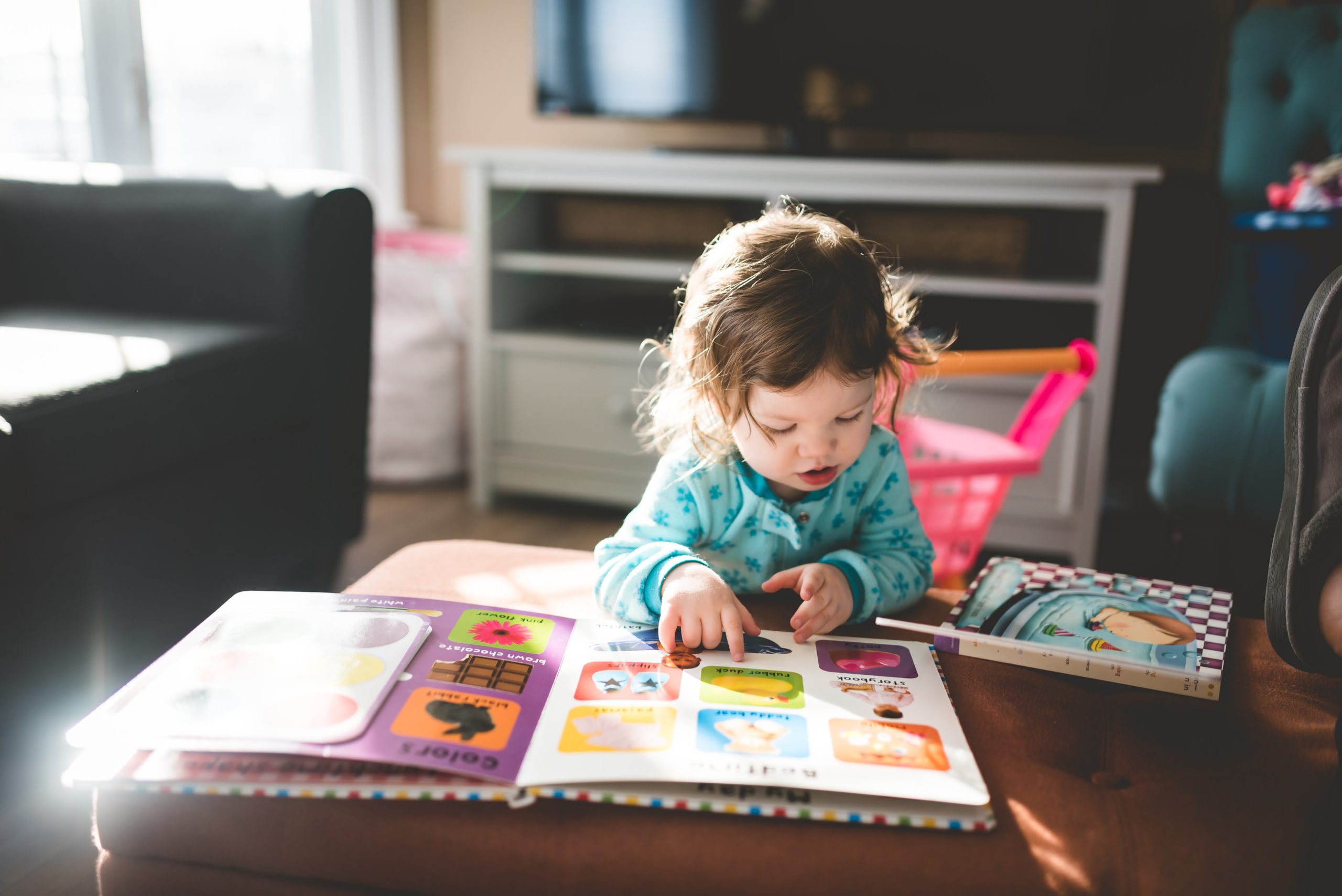 A child in a blue one piece is reading from a colourful picture book.